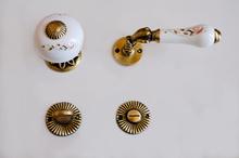 Дръжка розетка-топка месинг/порц.ст.злато110WC.
